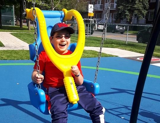 Un jeune garçon tout sourire dans une des nouvelles balançoires adaptées.