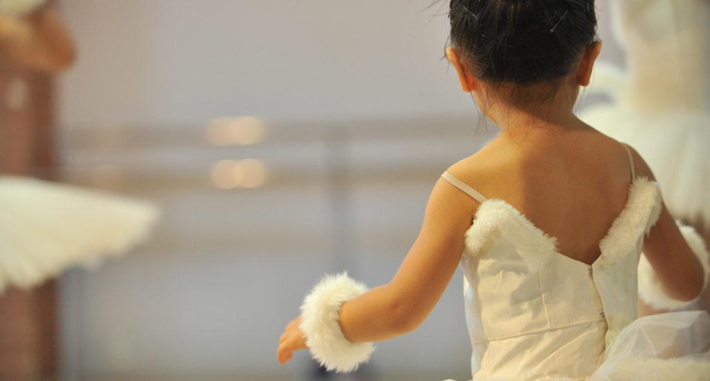 Petite ballerine vue de dos, en tutu et chignon.