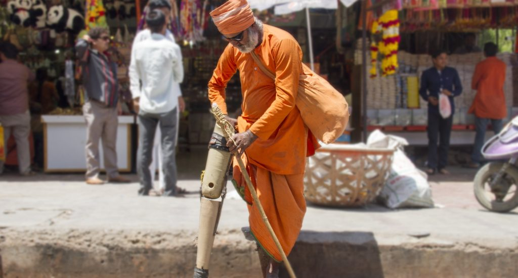 Un homme amputé à la jambe, qui porte un costume traditionnel de yogi orange,  ajuste sa prothèse sur le bord d'une rue en Inde.