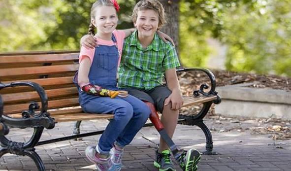Deux jeunes qui ont des prothèses colorées sont assis sur un banc.