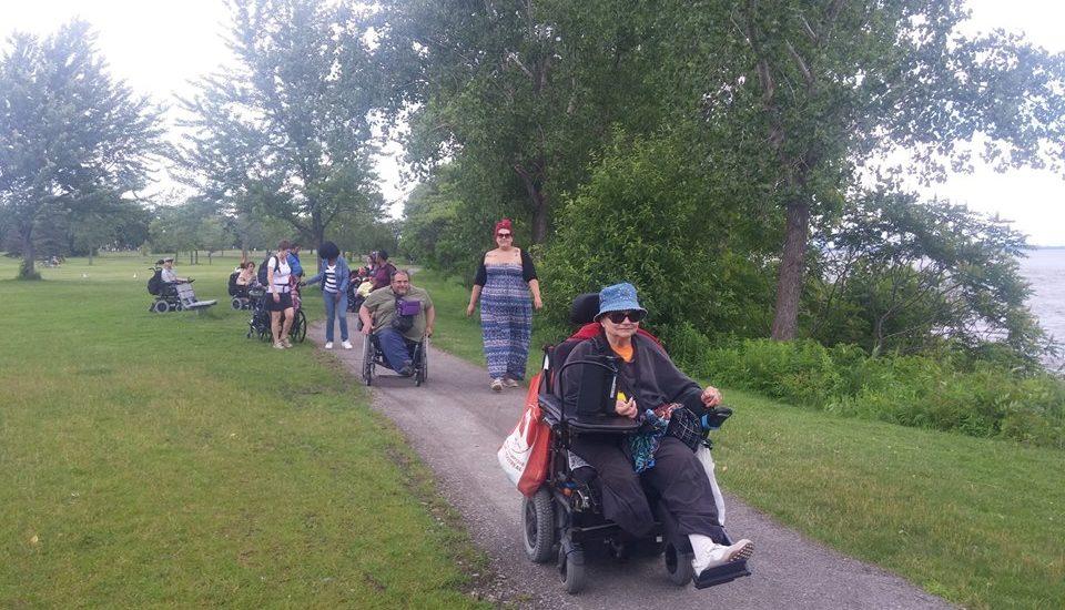 Des personnes en fauteuils roulant sur un sentier longeant le fleuve St-Laurent.