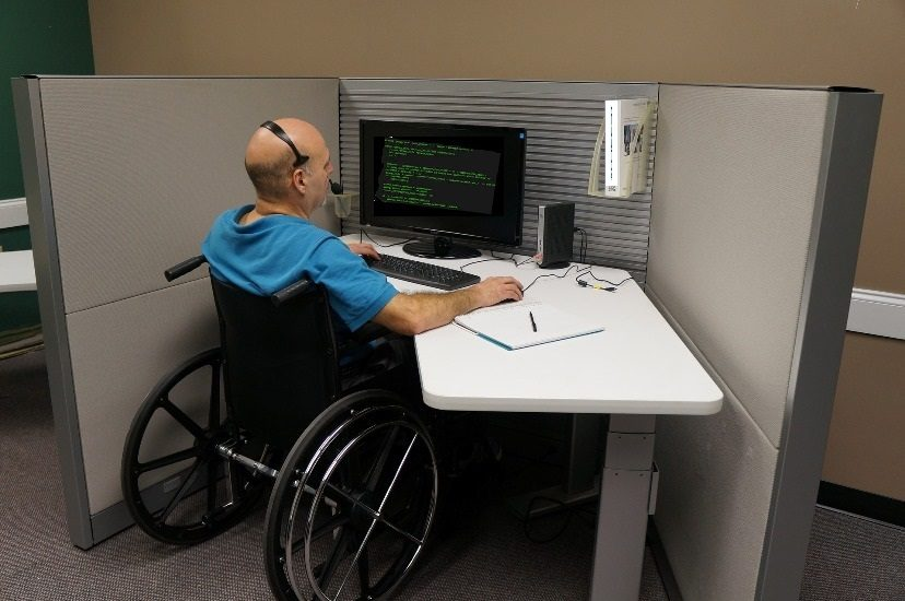 Un homme en fauteuil roulant travaille à un ordinateur dans un cubicule de bureau