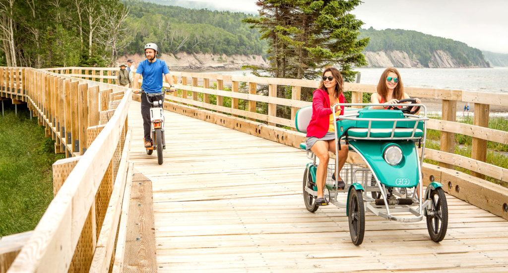 Trois personnes se baladent en vélo adapté
