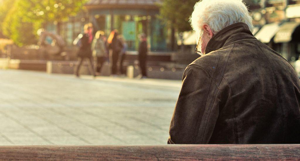 On voit de dos un homme aux cheveux blanc assis sur un banc, dans le centre d'une ville.