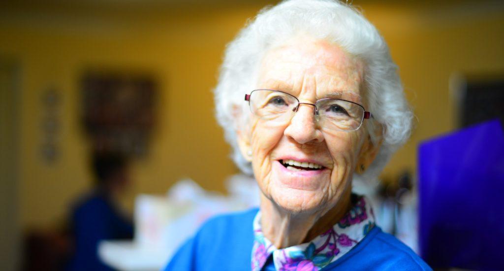 Une vielle dame aux cheveux blanc esquisse un sourire