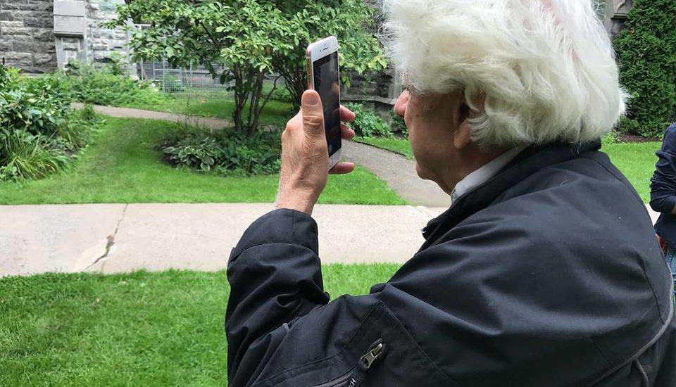 Un participant du rallye de l'INCA prend une photo avec son cellulaire.