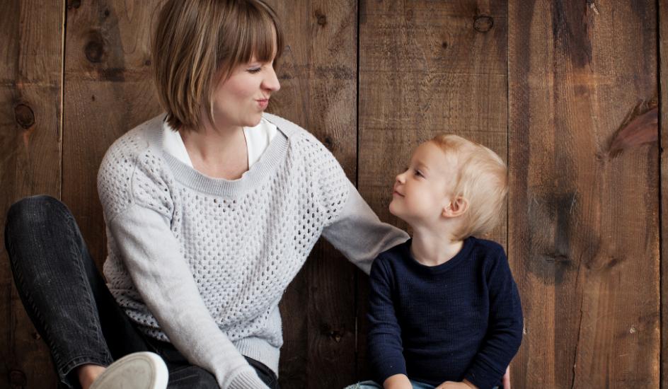 Une femme aux cheveux châtains avec un bambin aux cheveux très blonds, assis par terre.