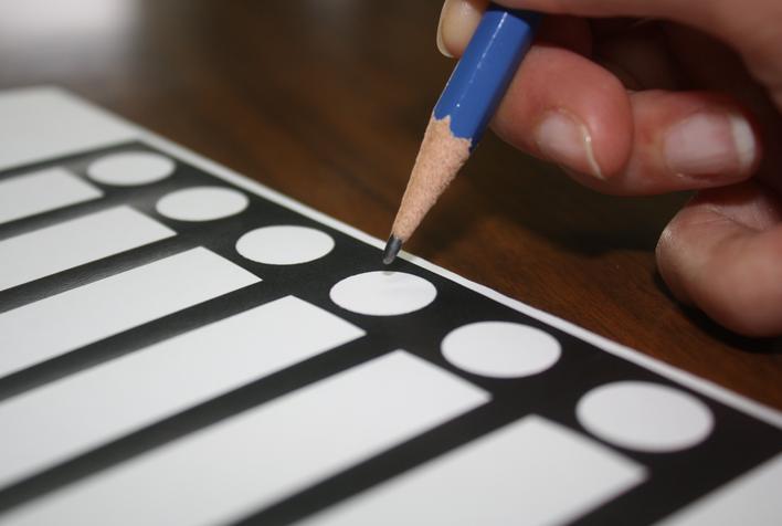 Un crayon à mine est posé sur une bulletin de vote, prêt à faire un X.