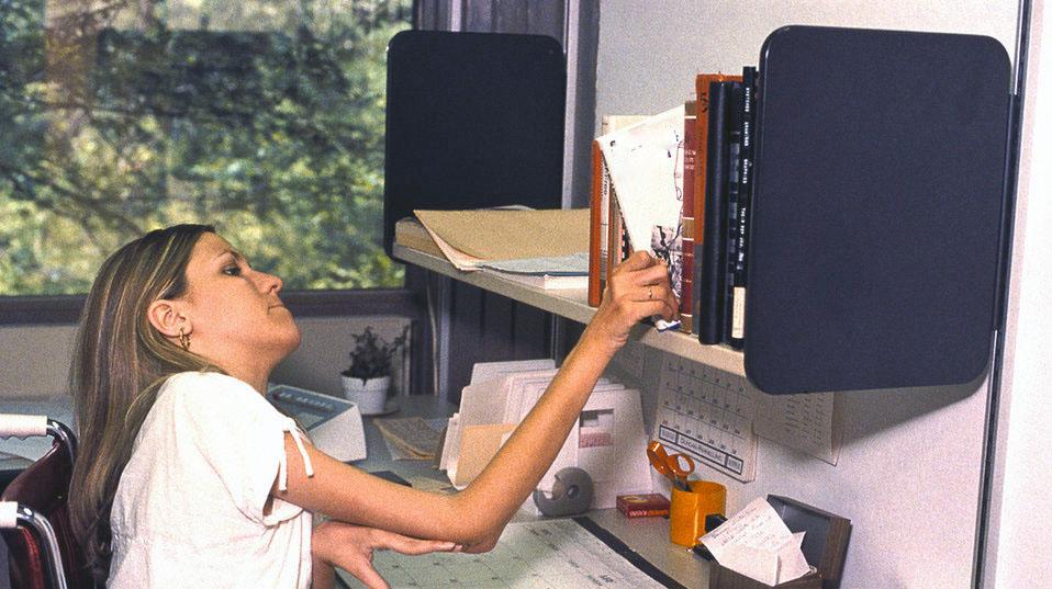 Une jeune femme en fauteuil roulant travail à un bureau.