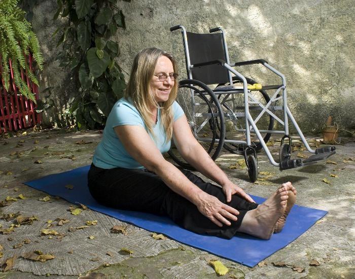 Une femme est assise sur un tapis de yoga, à côté d'un fauteuil roulant.
