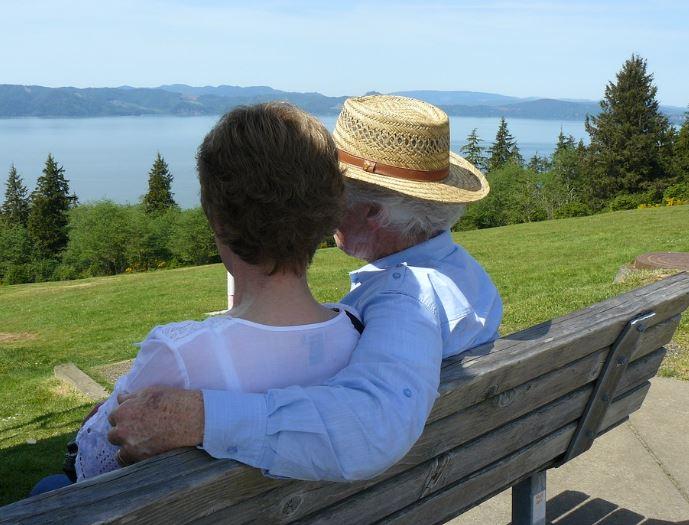Un homme et une femme (aînés) regardent le fleuve, sur un banc de parc .