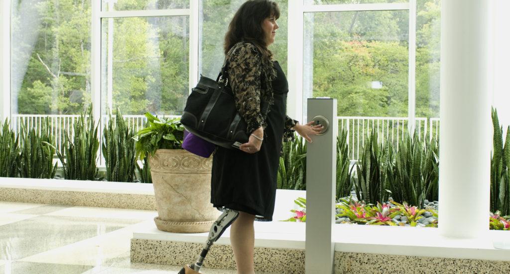 Une dame ayant une prothèse à la jambe appuie sur le bouton d'une porte automatique.