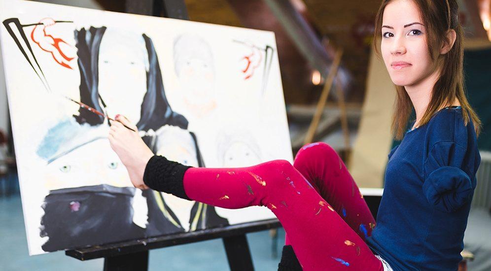 Une jeune amputée aux bras fait de la peinture avec ses pieds.