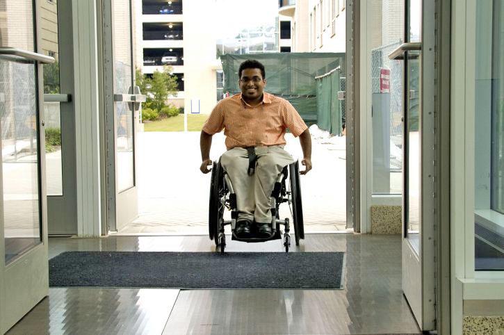 Un homme entre dans un édifice en fauteuil roulant.