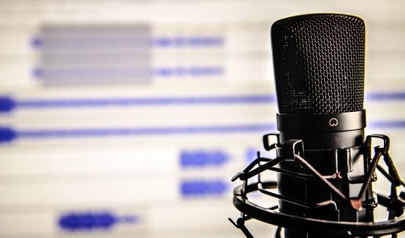 Un microphone de radio devant un écran d'ordinateur où l'on voir un logiciel de montage audio.