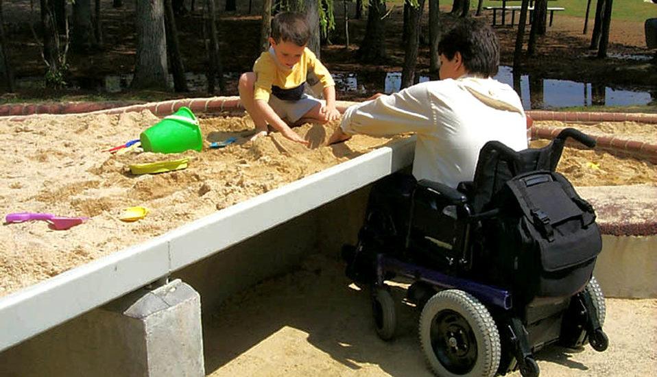 Un père en fauteuil roulant joue avec son petit garçon dans un bac à sable sur-élevé qui permet au fauteuil de se glisser dessous.