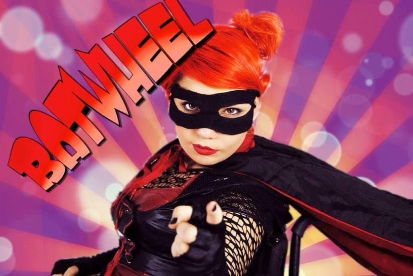 Maxime D.-Pomerleau dans son costume de Batwheel, porte un masque noir devant les yeux, a les cheveux rouge, et point vers l,avant avec son index.