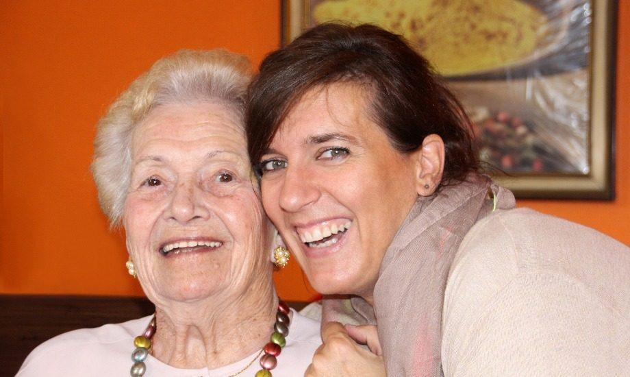 La photo montre deux dames, une plus âgée avec les cheveux blancs et l'autre plus jeune au cheveux bruns, qui sourient à la caméra.