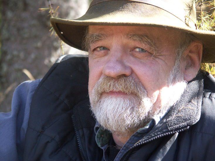Gros plan sur le visage de Serge Bouchard, qui porte une barbe presque complètement blanche et un chapeau en feutre marron.