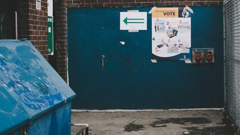 On aperçoit une flèche qui indique l'entrée d'un bureau de vote, dans ce qui ressemble à l'arrière d'une école.