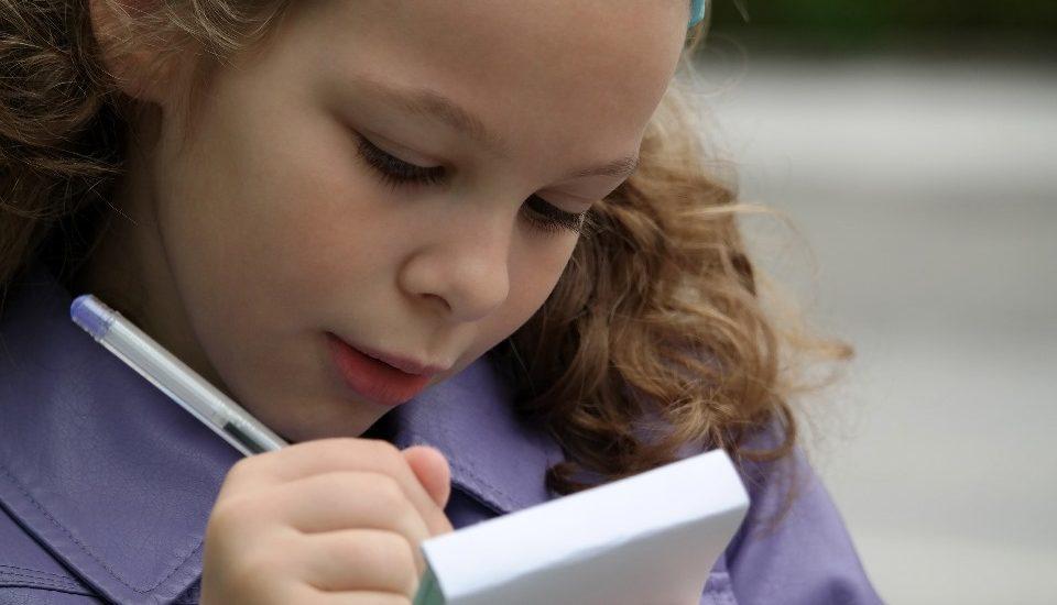 Une jeune fille blonde et frisée écrit sur un carnet avec un stylo.