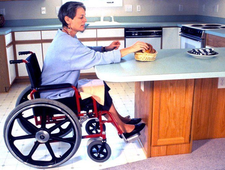 Une dame en fauteuil roulant prend un fruit sur le comptoir d'une cuisine. La hauteur du comptoir et l'espace dégagé sous celui-ci lui permet de le faire facilement .
