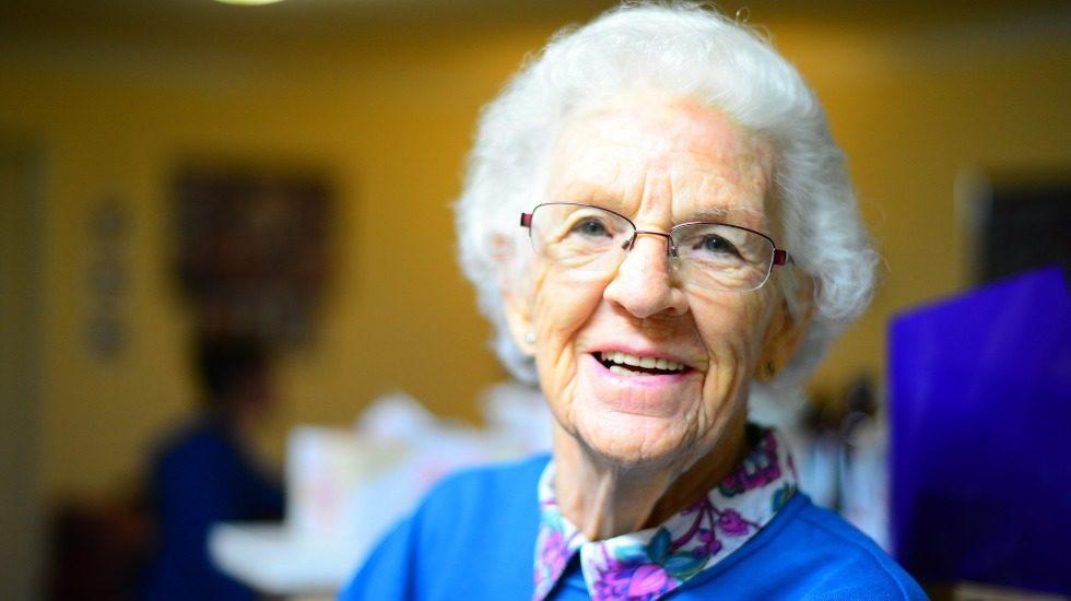 Gros plan d'une dame âgée aux cheveux courts et blancs, portant des lunettes, qui a un beau sourire.