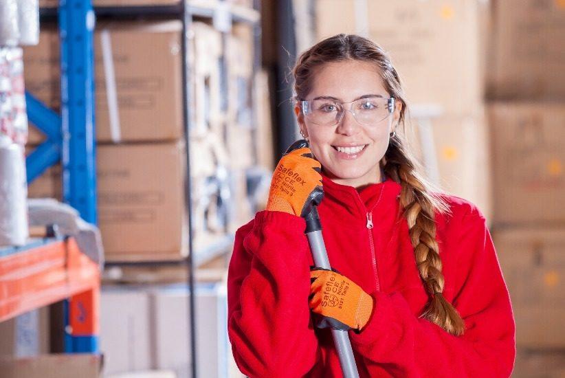 une femme porte un sarrau rouge, des gants oranges et des lunettes de protection. Elle tient ce qui semble être un ballet, dans un entrepôt oz des boites de carton son empilées.