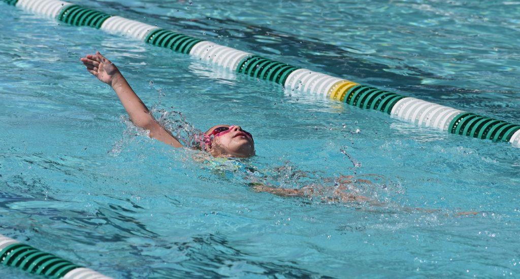 Un enfant qui porte des lunettes roses, nage sur le dos dans le corridor d'une piscine.