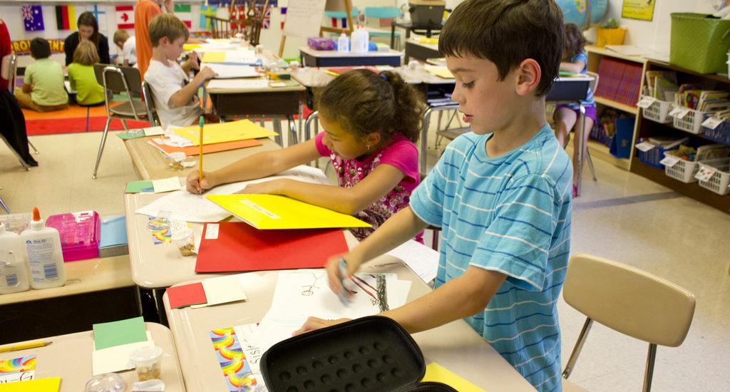 Des enfants font du bricolage sur des grandes tables dans une classe.