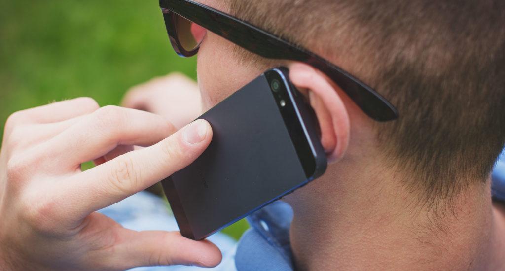 La photo montre le côté de la tête d'un homme (cheveux courts, verres fumés) qui tient un cellulaire à son oreille.