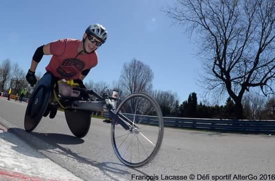 Lee Leclerc sur une  piste asphaltée, sur son fauteuil roulant de course.