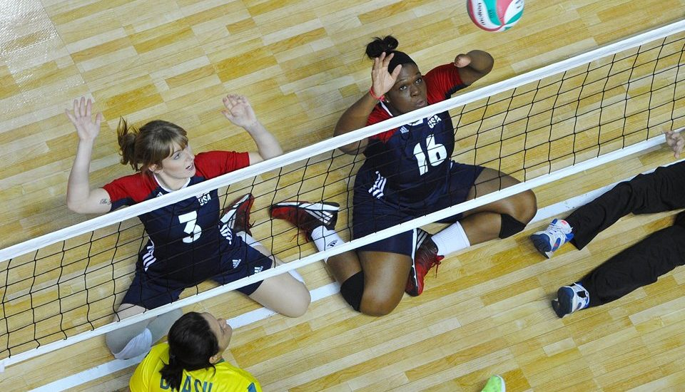 On aperçoit deux joueuses, les bras dans les air, assises à proximité du filet.