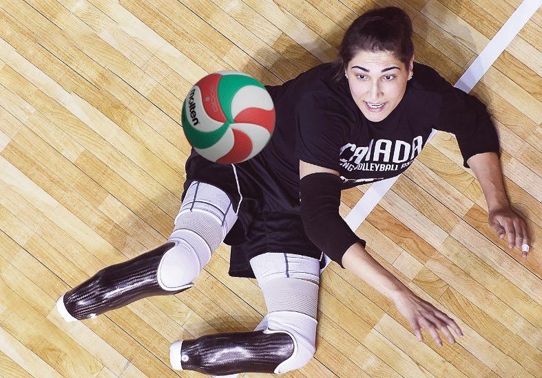 Une joueuse de volleyball amputée aux deux jambes regarde le ballon voler dans les airs.