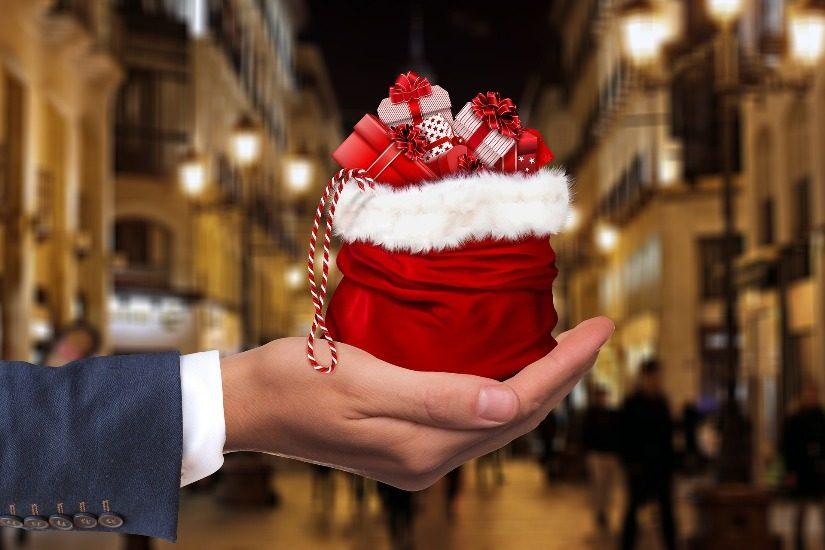 Dans une main d'homme (on devine à sa manche qu'il porte un habit), une bourse contient des cadeaux de Noël.