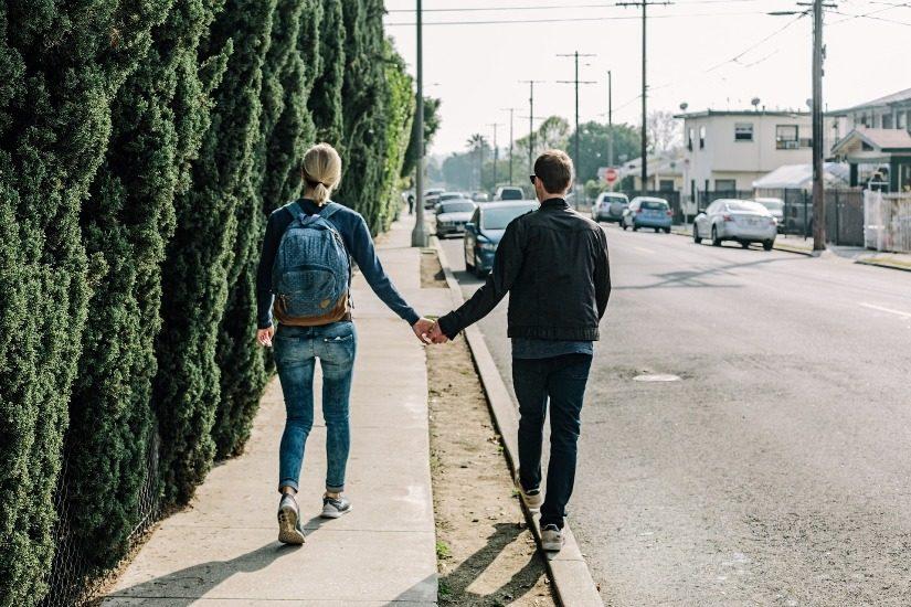 Une jeune femme et un jeune homme marchent sur le trottoir en se tenant la main.