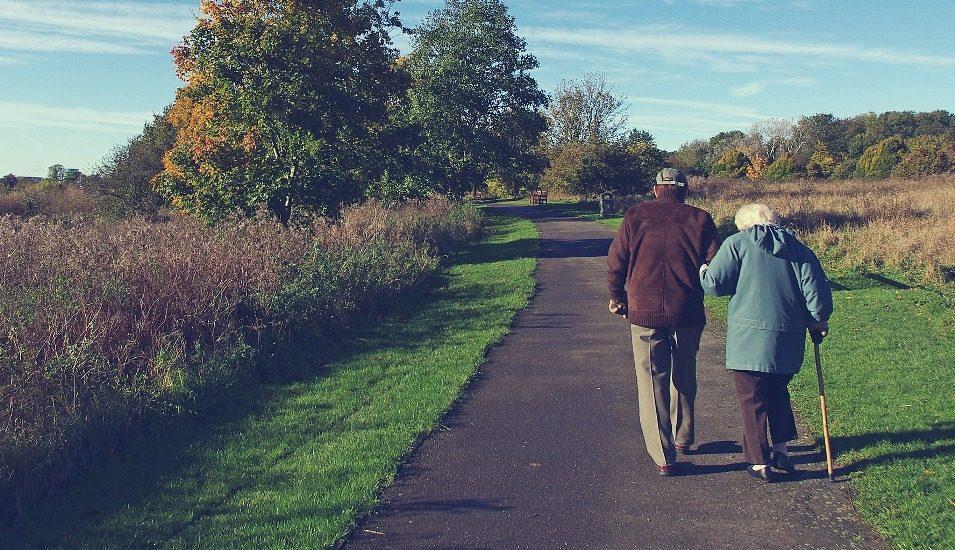 On voit de dos un hommes et une femme âgés qui marchent sur un sentier en bordure d'une forêt. La femme tiens le bras de l'homme et utilise une canne pour marcher.