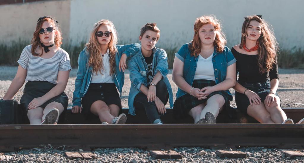 Plusieurs jeunes femmes aux poids variés posent assises sur une voie ferrée.