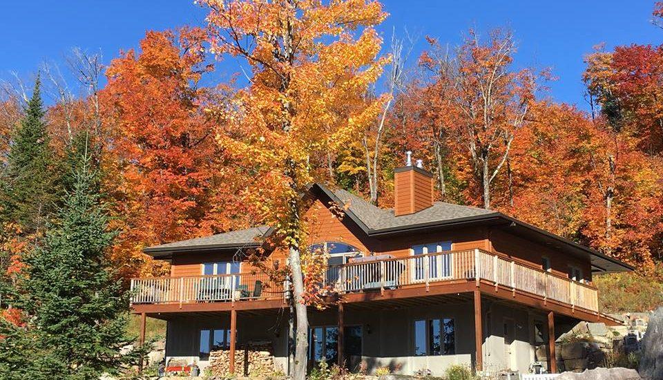 Le gite Vita Bella (un grand chalet en bois de deux étages) avec en arrière plan un paysage d'automne.