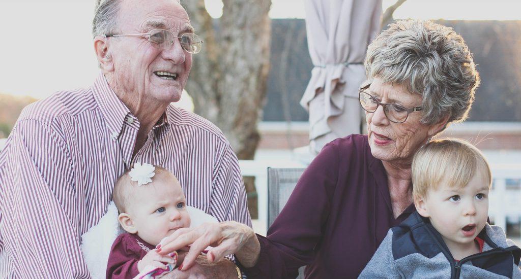 Un homme et une femme âgés (cheveux blancs, lunettes, ils ont des rides), tiennent un bébé et une petit garçon dans leurs bras.