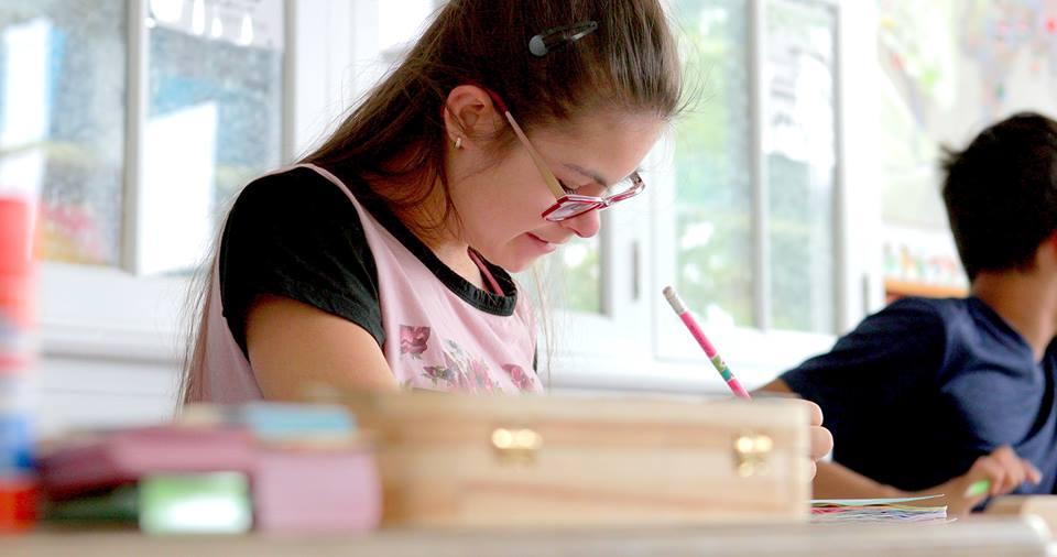 Une fillette portant des lunettes est penchée et écrit ou dessine.