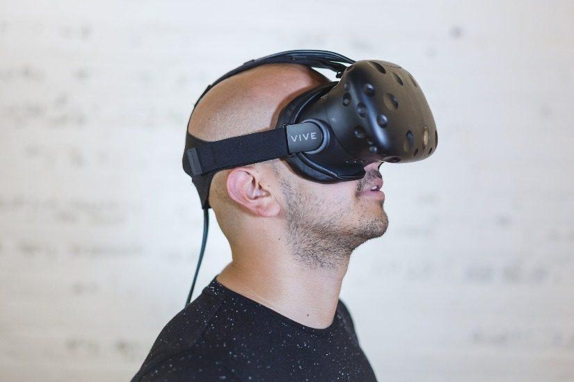 Un homme, chauve, porte un casque de réalité virtuelle sur les yeux.