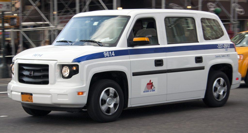 L'image montre une voiture blanche avec un logo indiquant qu'il s'agit d'un taxi adapté.