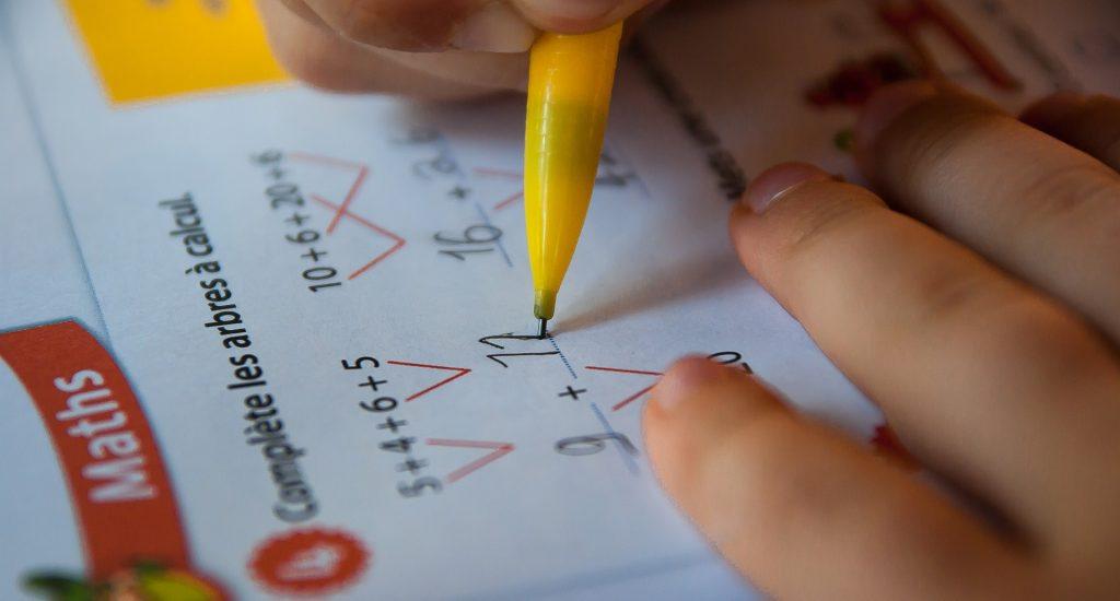 Gros plan sur un cahier de mathématiques sur lequel on aperçoit une main qui tient un crayon.