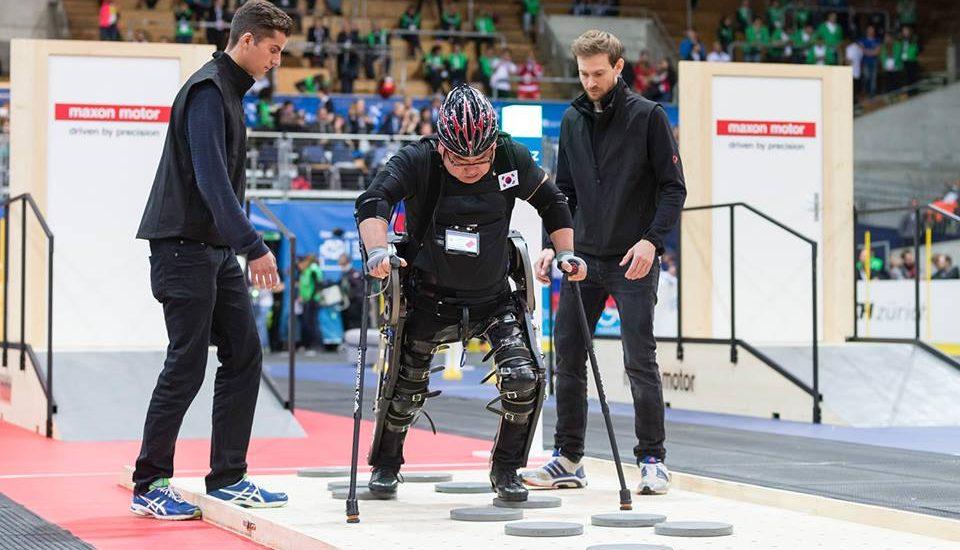 Un homme qui porte un exosquelette aux jambes, marche avec des béquilles sur un parcours de rondelles grises au plancher.