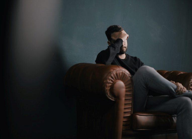 Un homme assis sur un divan a le front appuyé sur sa main et on ne voit pas ses yeux.