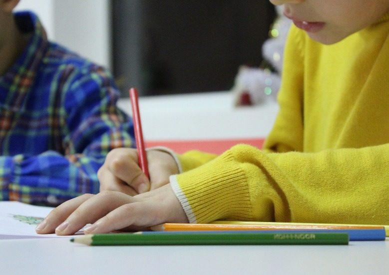 Un enfant s'applique à écrire avec un crayon rouge.