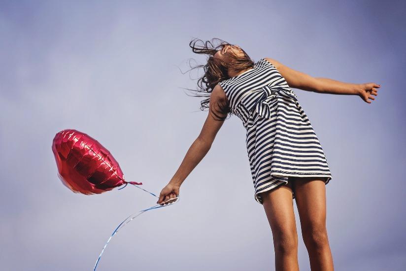 Une femme en robe d'été tient dans ses mains un ballon rouge en forme de coeur.