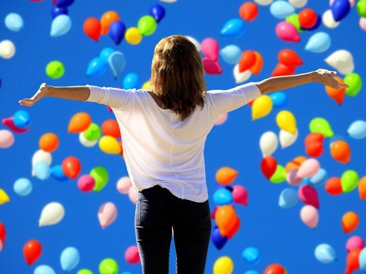 On voir une femme de dos et pleins de ballons multicolores sur un ciel très bleu.