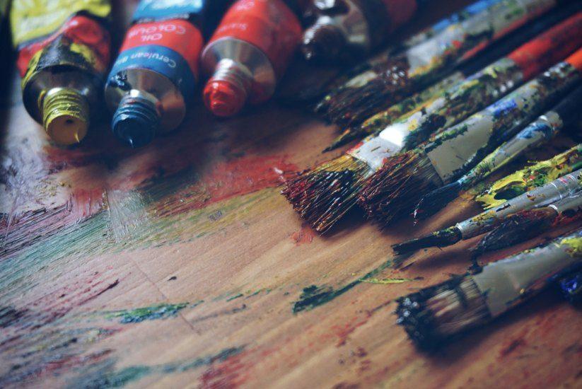 On aperçoit sur la photo des tubes de peintures et des pinceaux de peintre, avec de la couleur.